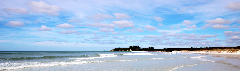Meeresbucht mit sanften Wellen und Sandstrand
