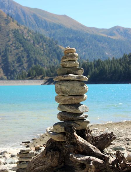 Turm aus Steinen vor tiefblauem Wasser